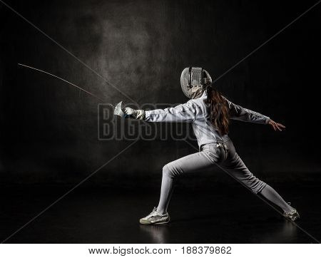 Female fencer wearing white fencing costume isolated on black background
