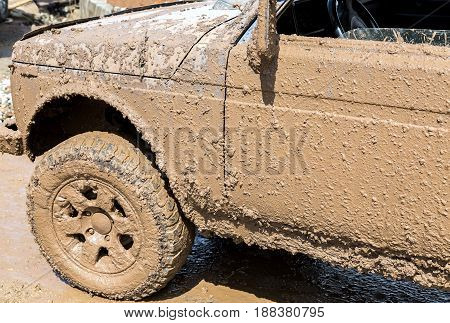 Off-road vehicle after driving in the rain on extremely dirty rural road