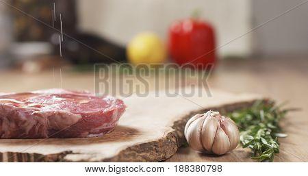olive oil pour onto raw rib eye steak on board, wide photo