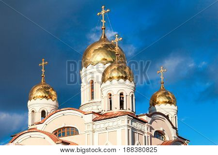 White orthodox church with golden domes against the dark blue sky