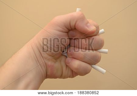 The hand clenches a fist and crushes the cigarettes to stop smoking