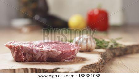 raw rib eye steak on board, wide photo