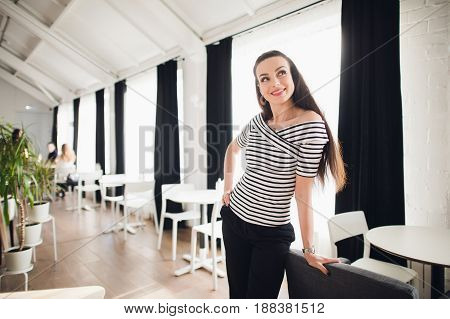 Beautiful woman standing indoors near table and looking away.