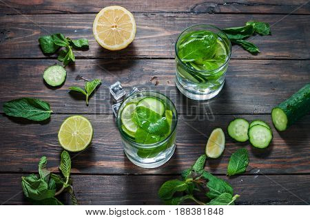 Cold and refreshing infused detox water with lime mint and cucumber in a glass on wood background. Top