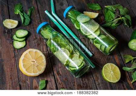 Cold and refreshing infused detox water with lime mint and cucumber in a bottle on wood background.