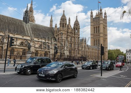 LONDON UK - APRIL 25 2017: Traffic on Abingdon St with House of Lords in the background.