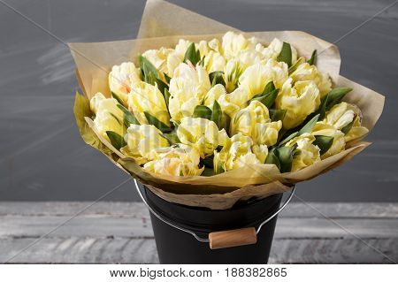 gently yellow pastel colors tulips in vase on wooden table. Gray wall.