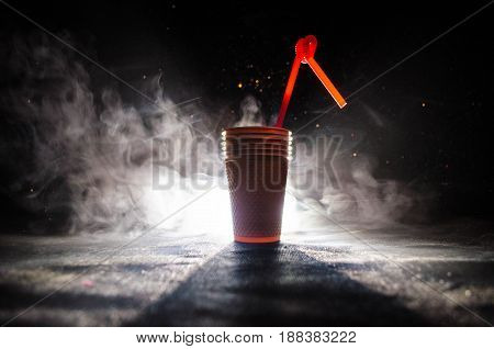Stack Of Orange Plastic Cups With Straw On Dark Background