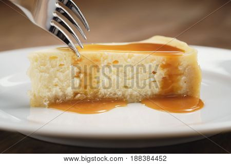 cheesecake with caramel sauce on plate closeup eaten with fork, shallow focus