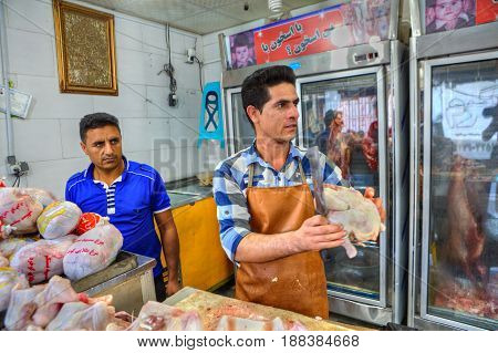 Bandar Abbas Hormozgan Province Iran - 16 april 2017: A meat shop near the grand oriental bazaar the worker cuts off chicken carcasses.