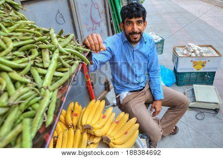 Bandar Abbas Hormozgan Province Iran - 16 april 2017: The vegetable merchant smiles sitting next to his goods