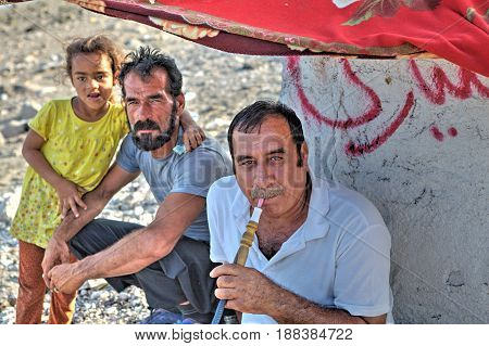 Bandar Abbas Hormozgan Province Iran - 16 april 2017: Two adults man and one child girl relaxing outdoors in the shade of an awning a man smokes a hookah.