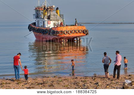 Bandar Abbas Hormozgan Province Iran - 16 april 2017: The townspeople are walking along the beach of the Persian Gulf against the backdrop of a towboat that ran aground.