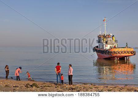 Bandar Abbas Hormozgan Province Iran - 16 april 2017: Iranian people walk on the beach of the Persian Gulf in the background the towing vessel which ran aground.