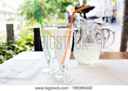 Lemonade, a refreshing drink in glass. City cafe, street background