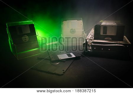 Pile Of Black Floppy Disks On Dark Background With Light. Vintage Computer Attributes