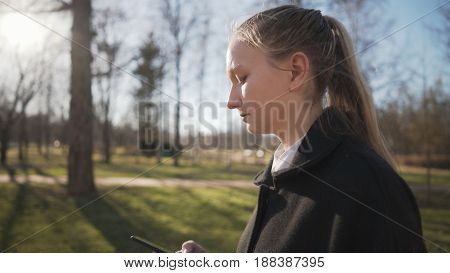 female teen girl using smartphone and walking in town park in spring sunny day, with copy space