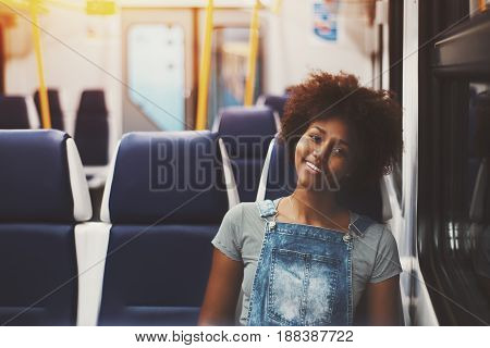 Cheerful charming black girl with curly afro hair in jeans overalls sitting in coach of empty suburban train while travelling home alone in evening with copy space for text logo or your advertising
