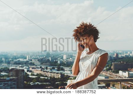 Cheerful young black model girl in simple dress is speaking via smartphone with her agent while standing on balcony of skyscraper hight floor with cityscape behind and copy space for text or your logo