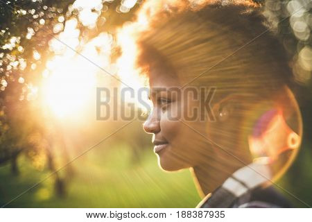 Art tilt-shift portrait of young charming black girl with curly afro hair illuminated with sun backlight during stunning summer sunset with real lens flares and chroma hoops copy space for your text poster