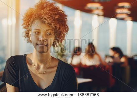 Portrait of young charming afro american female with curly hair sitting in office bar during coffee break with blurred silhouettes of colleagues in background and copy space for text or your logo