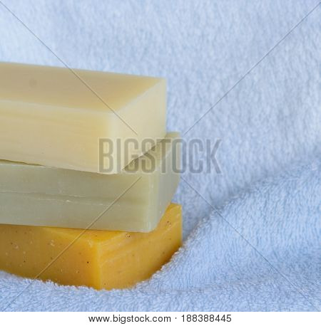 Stack of handmade soap bars on blue bath towel background