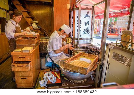 Tokyo, Japan - April 19, 2017: chef making japanese teriyaki famous dessert on Nakamise-dori, a street with food and souvenirs shops, in Senso-ji Buddhist Temple, Asakusa.