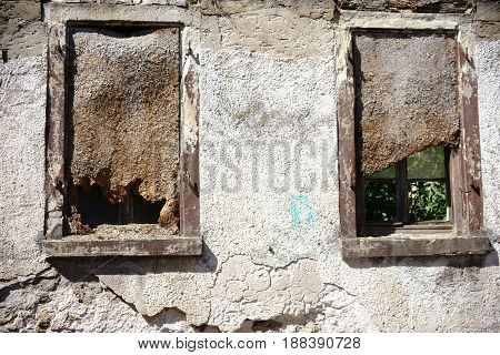 Two nailed windows in a ruin wall.