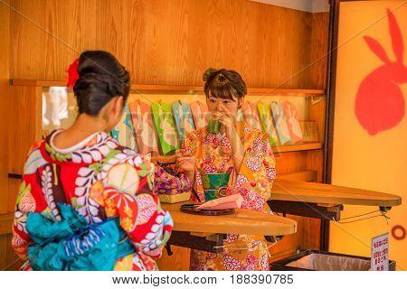 Tokyo, Japan - April 19, 2017: two young women in traditional japanese kimonos drink Amazake inside a famous stand selling Kibi-dango on Nakamise-dori street at Senso-ji Temple, Asakusa.