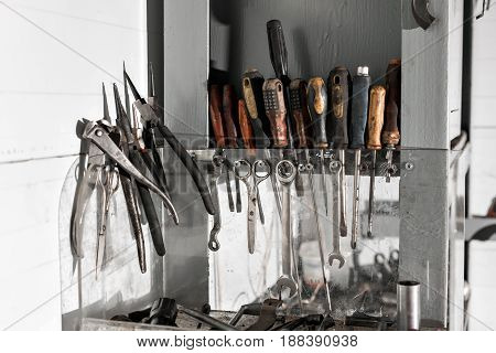 assortment of do it yourself working tools hanging in a cupboard against a wall. dirty engine oil.