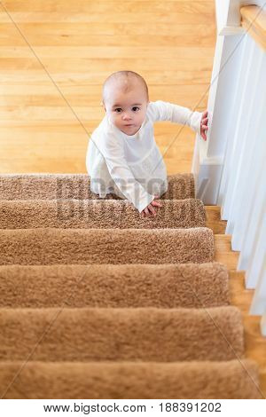 Happy Toddler Girl Climbing The Stairs In Her House