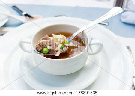 A bowl of delicious beef and barley soup with carrots, tomato, potato, celery, and peas
