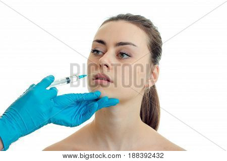 cosmetologist makes prick near the lips a young pretty girl close-up isolated on white background