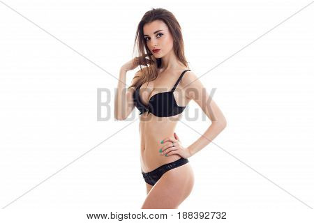 slender sexy girl in black underwear and with red lipstick poses on camera isolated on white background