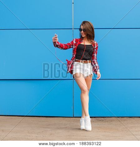 Fashion portrait of pretty smiling hipster girl in sunglasses with smartphone and headphones making selfie against the colorful blue wall.