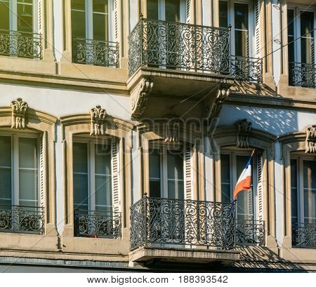 French national Flag tricolore hanged on a French balcony building on a sunny day