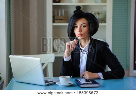 Business Lady With Glasses Dressed In Black Suit Working On A Laptop