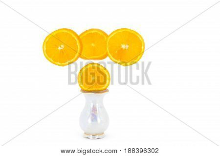 Orange slices, fixed in a vase as flowers, in a graceful small vase isolated on white background