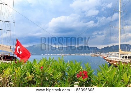 Oleander flowers and turkish flag in the seaport of marmaris with mountains background
