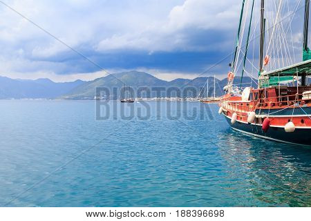Boat in the seaport of Marmaris with mountains over clouds
