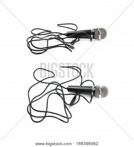 Black microphone lying over its own cord, composition isolated over the white background, set of two different foreshortenings