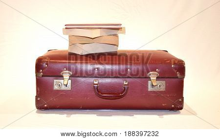 vintage red old suitcase valise with brass buckles and four books lying on top