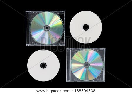 Four CD on black background isolated. Top view