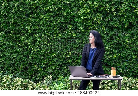 Asian Busineswoman using laptop computer working outside office at green hedgeMoblie office concept.