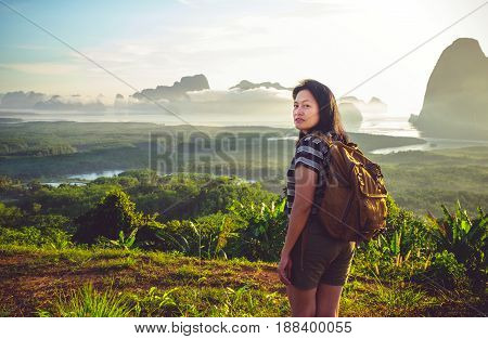 Happy young traveler woman backpacker looking backward to camera with a beautiful of nature at top of mountain view point and sea. Freedom wanderlust. Khao Samed Nang Chee Viewpoint Phang Nga Thailand.