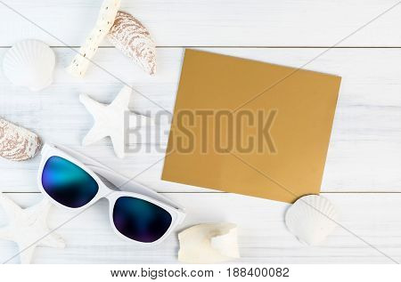 Summer Beach accessories (White sunglassesstarfishstraw hatshell) and gold color paper note card on white plaster plank wood table top viewSummer vacation conceptLeave space for adding your text