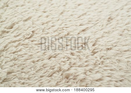 Close-up fragment of an artificial beige colored fur texture as a backdrop composition with a shallow depth of field