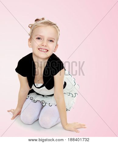 Beautiful little blonde girl dressed in a white short dress with black sleeves and a black belt.Girl sitting on the floor leaning on hands and smiling at the camera.Pale pink gradient background.
