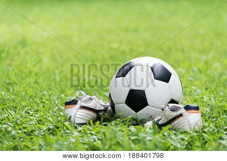 football on green grass and stud shoe healthy concept