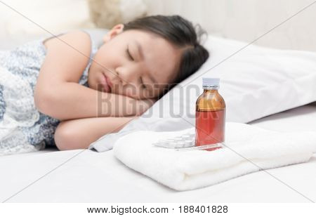 Sick Girl Lying In Bed And Medicine Syrup